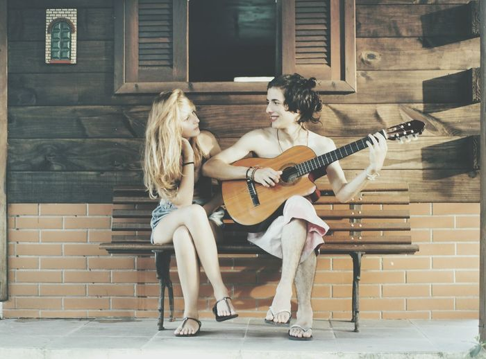 Boy playing guitar with girl