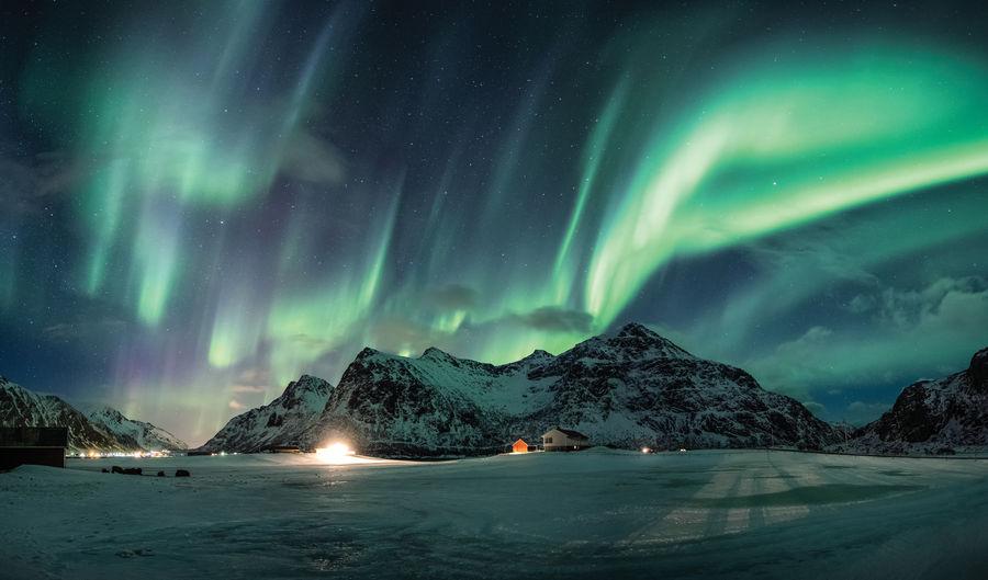 Landscape against aurora polaris at night