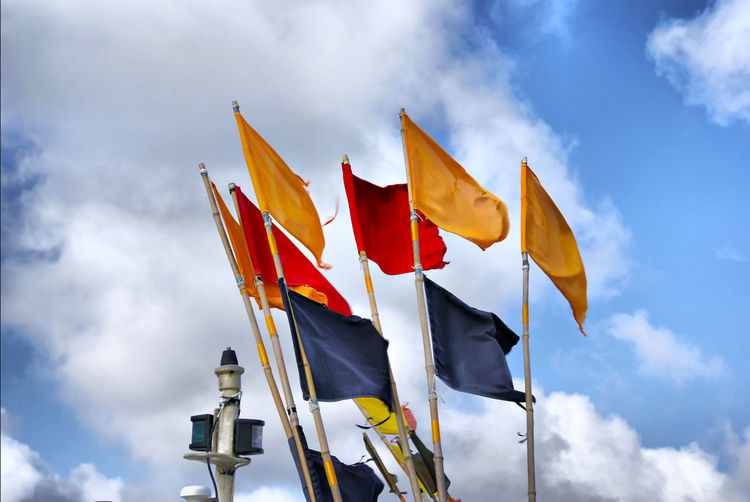 Blue Flag Cloudy Red Stormy Weather Weather Blue Blue Sky Cloud - Sky Clouds Clouds And Sky Day Flag Flags Flags In The Wind  Low Angle View No People Outdoors Patriotism Red Flag Sky Symbol Symbolic  Symbolism Yellow Yellow Flag