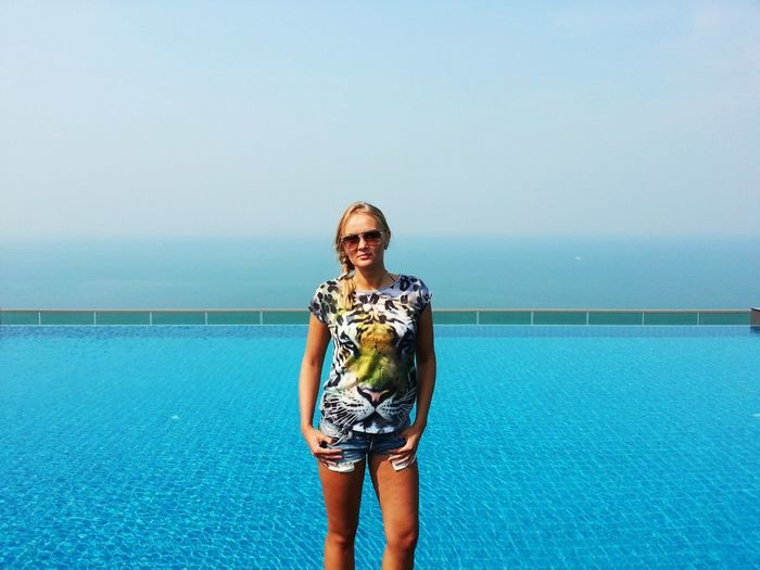 Portrait of beautiful woman standing at swimming pool standing against sea