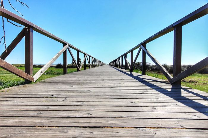 The Way Forward Bridge - Man Made Structure Railing Outdoors Wood - Material Boardwalk Built Structure Footbridge Connection No People Wood Paneling Day Boardwalk Photography Boardwalk Scapes Low Angle View Low Level Shot Low Level Photography Wooden Walkway Wooden Walking Bridge Bridge Blue Sky Clear Sky Conil De La Frontera Conil Conildelafrontera