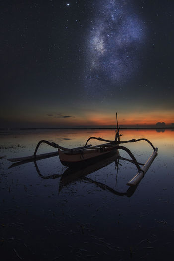 Boat in lake against sky at night