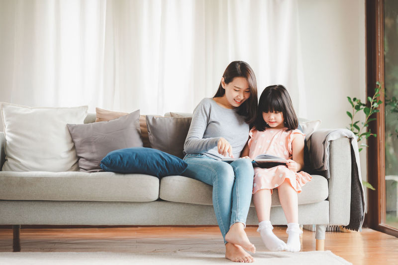 Full length of mother and daughter sitting on sofa