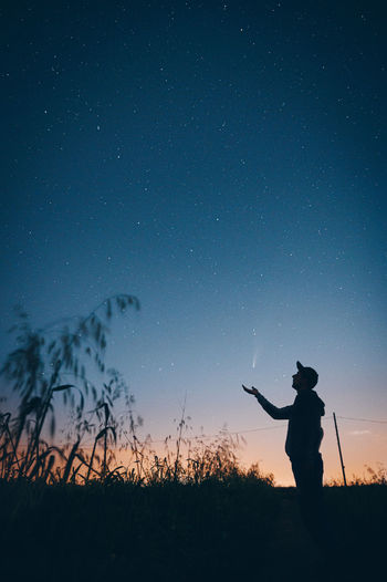 Silhouette man standing on field against sky at night catching a shooting star