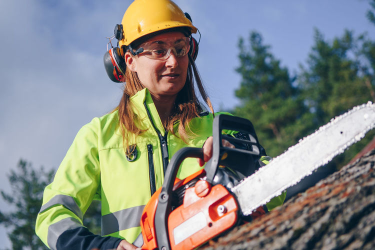 Female lumber worker with chainsaw Diversity Females Work Workplace Adult Adults Only Adventure Chainsaw Close-up Day Focus On Foreground Front View Hardhat  Headwear Helmet Lifestyles Looking At Camera Lumber Nature One Person Outdoors People Portrait Real People Reflective Clothing Safety Sky Standing Young Adult