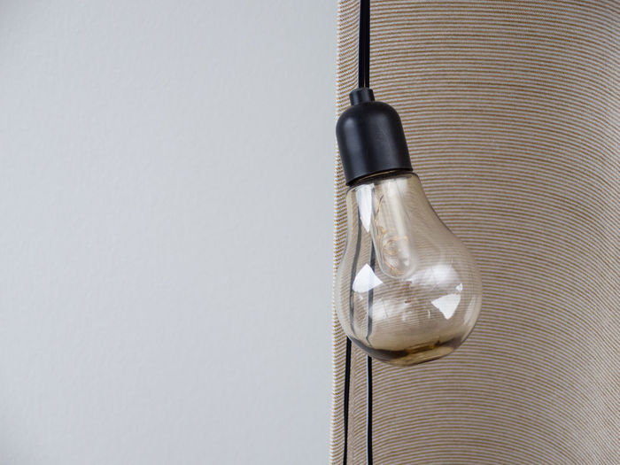 High angle view of light bulb hanging on table against white background
