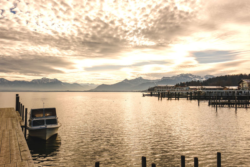 Sky Nautical Vessel Water Cloud - Sky Mode Of Transportation Beauty In Nature Transportation Sunset Mountain Scenics - Nature Tranquil Scene Tranquility Nature No People Reflection Moored Lake Mountain Range Idyllic Outdoors Wooden Post Bay Chiemsee
