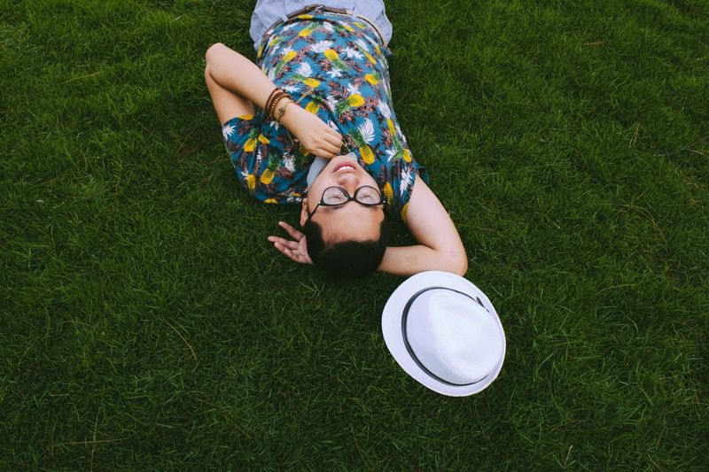 High angle view of young man lying on field in park