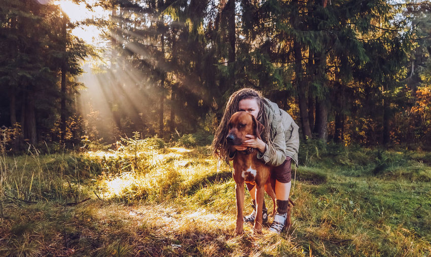Young smiling woman with dreadlocks in autumn fall forest in the morning sunshine playing with a dog ridgeback Tree Plant Mammal Domestic Animals One Person One Animal Domestic Pets Real People Animal Themes Land Animal Nature Lifestyles Leisure Activity Vertebrate Canine Dog Forest Outdoors Pet Owner Hairstyle Dreadlocks Ridgeback