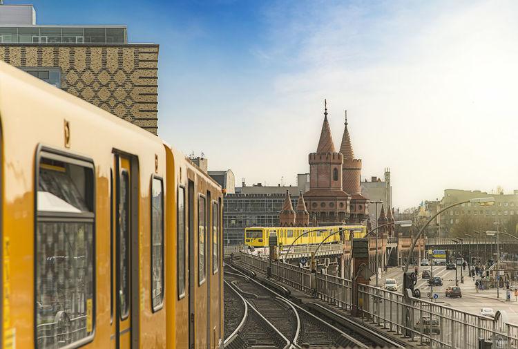 Subway Train On Railroad Tracks By Oberbaumbruecke Against Sky