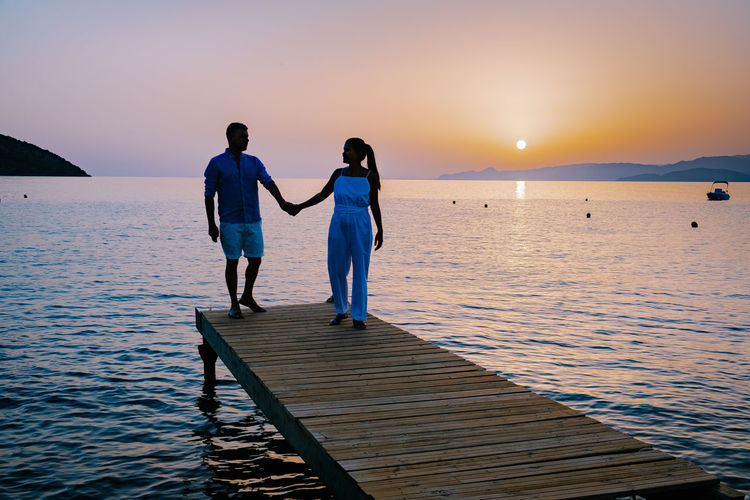 Rear view of couple standing on sea against sky during sunset