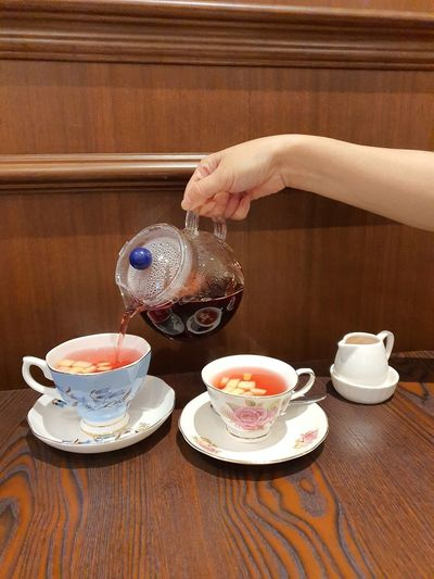 Hand holding tea cup on table