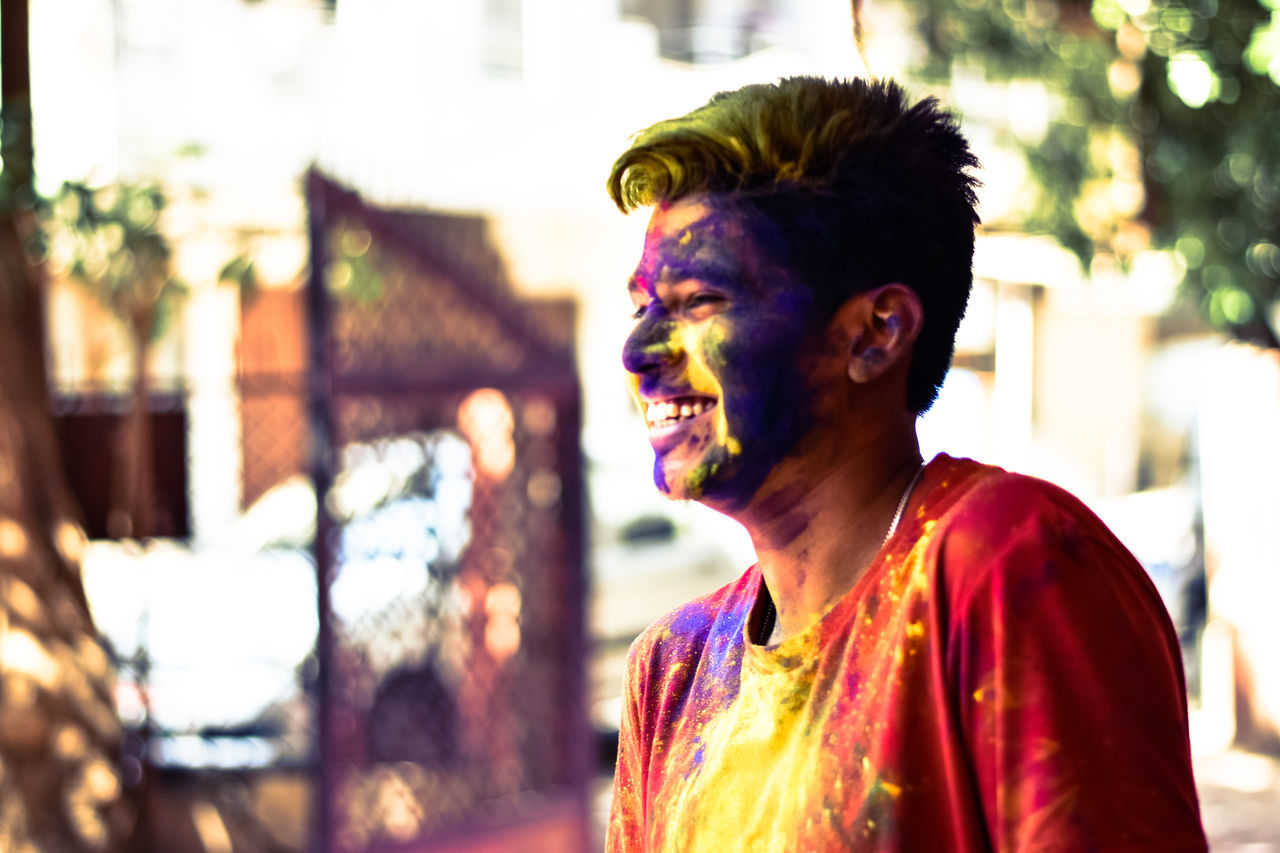 face paint, celebration, holi, happiness, focus on foreground, real people, one person, traditional festival, cultures, powder paint, event, fun, lifestyles, smiling, outdoors, body paint, multi colored, headshot, young adult, leisure activity, make-up, cheerful, day, standing, portrait, halloween, adult, people