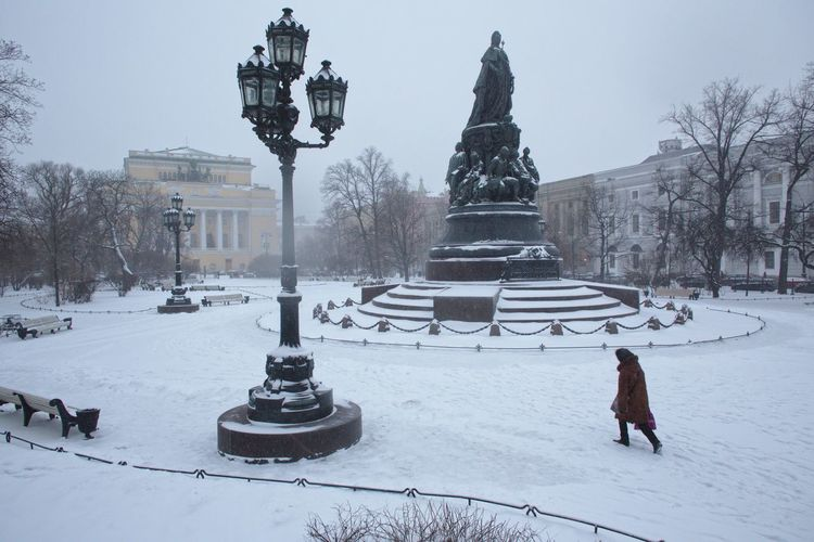 Woman Walking On Snow By Catherine The Great Monument In City During Winter