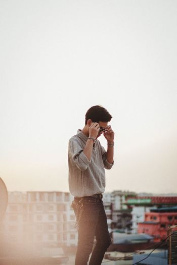 Young man standing in city against clear sky at sunset