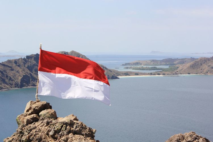Indonesian Flag Island Flags In The Wind  Flag Flags Flagstaff Mountain Flags Of The World Water Sea Snow Cold Temperature Winter Red Beach Sky Horizon Over Water National Flag National Icon Patriotism Rocky Mountains Archipelago Coastline Coast Lagoon Flag Pole Fluttering