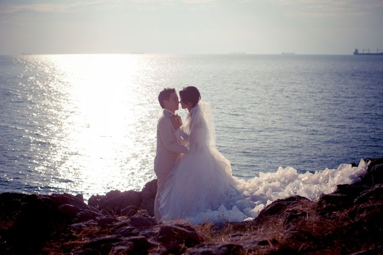 Side view of bride and bridegroom standing face to face at beach