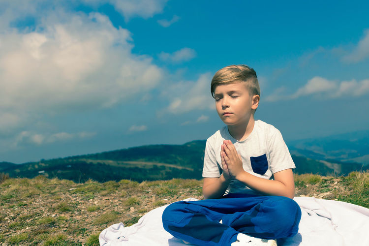 Boy sitting on mountain against sky