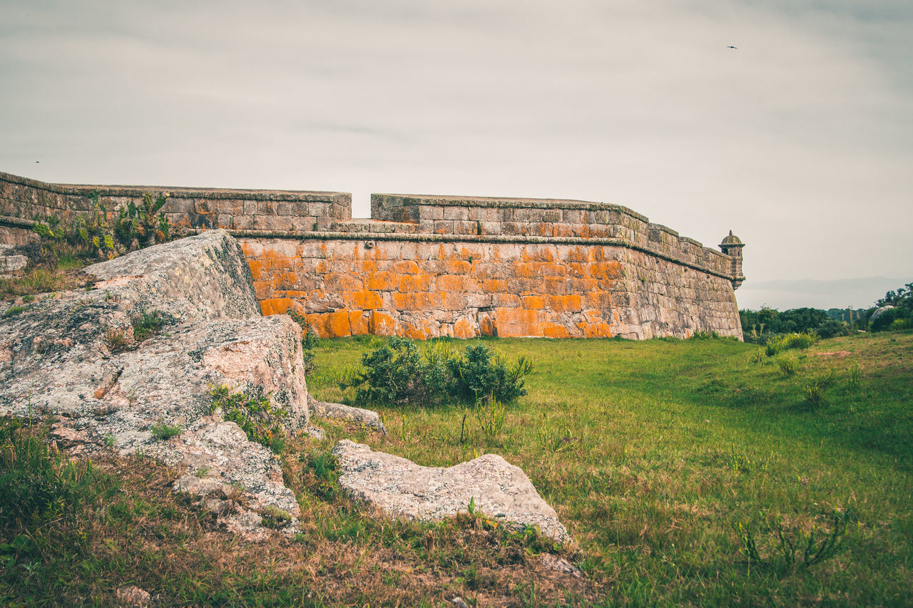 sky, history, the past, plant, architecture, built structure, nature, grass, day, ancient, no people, old, cloud - sky, land, old ruin, travel destinations, building exterior, tranquility, solid, rock, outdoors, archaeology, ancient civilization, ruined