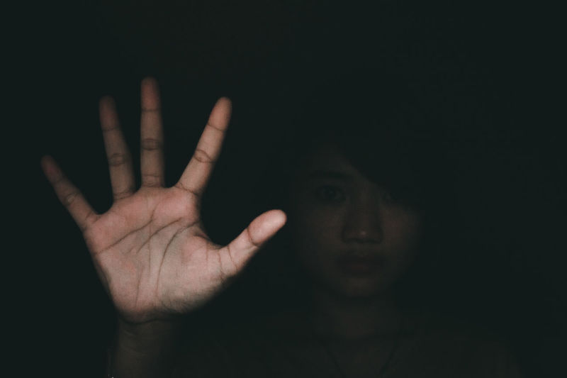 Portrait of young woman gesturing against black background
