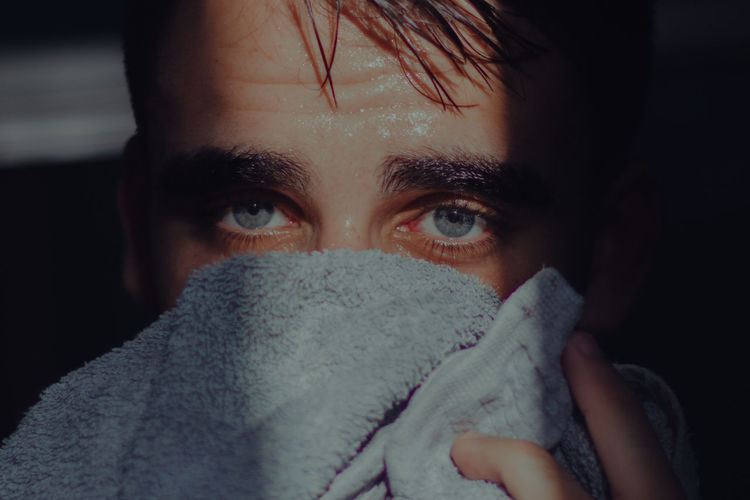 Close-Up Portrait Of Young Man Covering Face With Towel At Home