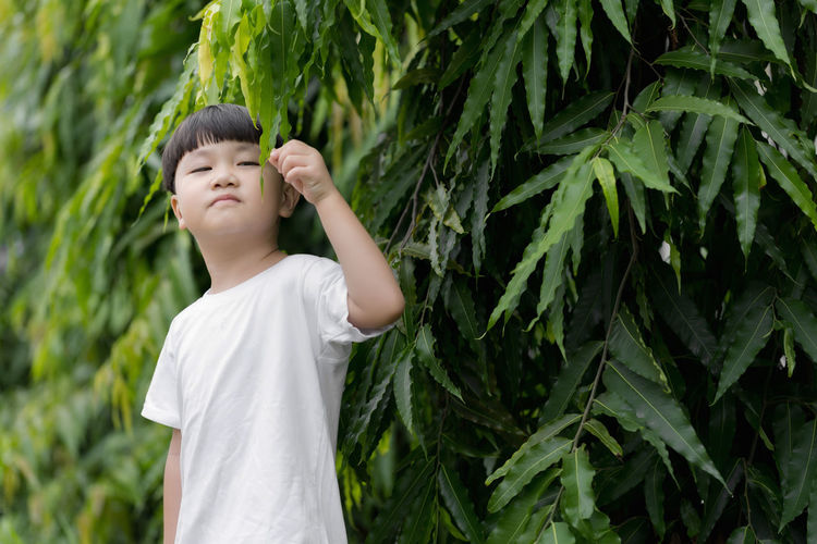 Boy standing against plants