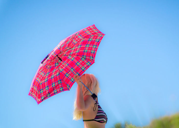 Side view of woman holding umbrella while standing against clear blue sky