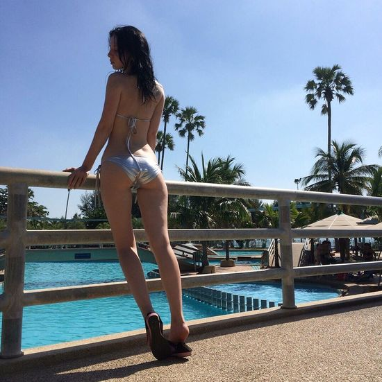 Swimming Pool Water Railing Palm Tree Young Adult Young Women One Person Full Length Summer Day Outdoors Sky Leisure Activity Sunlight Women One Young Woman Only Vacations Tree Standing Beautiful Woman