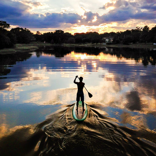 Silhouette of paddle boarder at sunset Adventure Escapism Getting Away From It All Light Outdoors Recreational Pursuit Reflection Sunset Sunset #sun #clouds #skylovers #sky #nature #beautifulinnature #naturalbeauty #photography #landscape Sunset Silhouettes Tranquil Scene Water Weekend Activities Market Bestsellers 2017