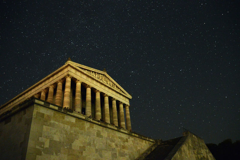 Low angle view of historic building against star field
