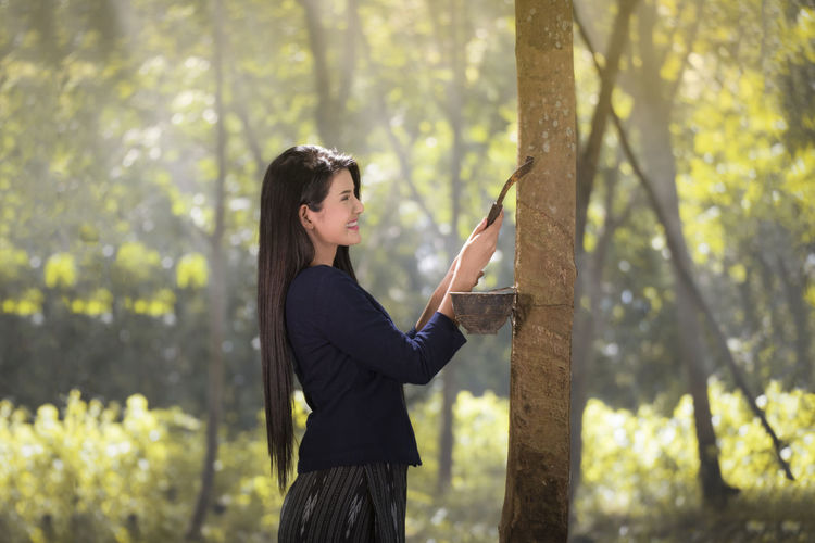 Side view of young woman standing in forest