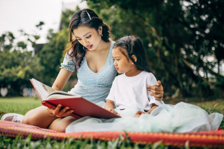 Smiling teacher and girl reading book sitting at park