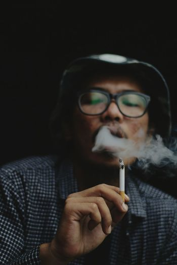 Low angle view of young man smoking cigarette against black background