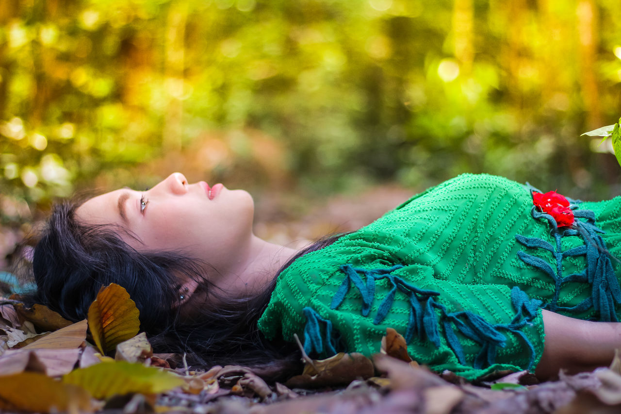 one person, lying down, real people, lifestyles, leisure activity, selective focus, relaxation, child, childhood, women, young women, eyes closed, nature, headshot, focus on foreground, day, leaf, plant part, outdoors, innocence, change, contemplation