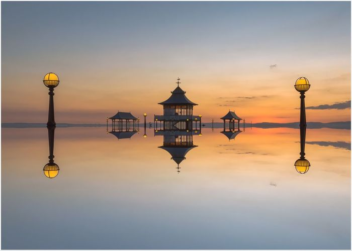 Clevedon Pier reflected EyeEm Selects Sky Sunset Water Symmetry Architecture Reflection No People Built Structure Beauty In Nature Nature Street Light Waterfront Lighting Equipment Building Exterior Scenics - Nature Orange Color History Idyllic The Past Textured Effect