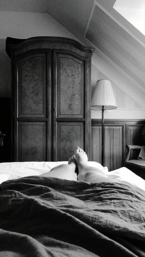 Low section of woman relaxing on bed at home