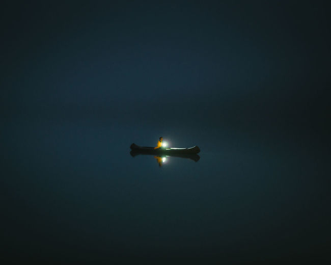 Low angle view of illuminated airplane against sky at night