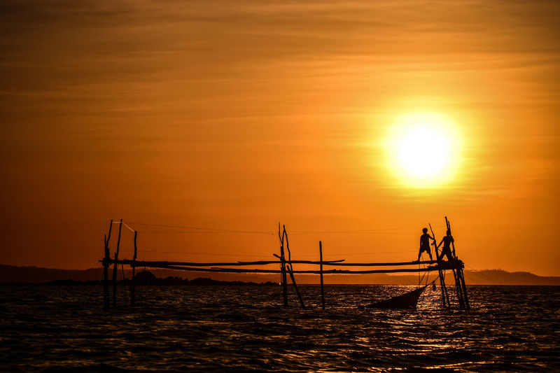 Fishermen setting up the fish cage. Bicol Bicolandia Bicolandia2016 Dramatic Sky Fish Cage Fisherman Landscape Majestic Nature Orange Color Philippines Scenics Sea Seascape Silhouette Sky Sun Sunset Tourism Tranquility Vacations Water Waterfront