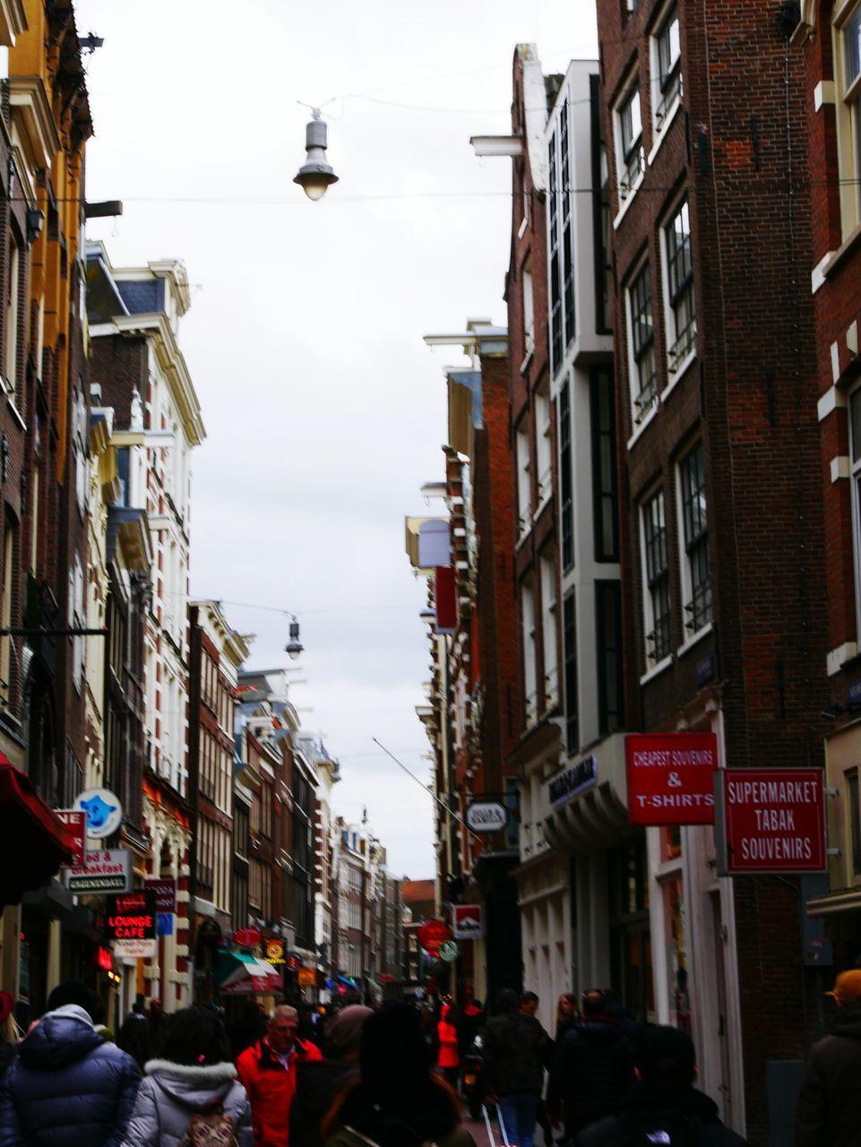 Crowd On City Street Amidst Buildings Against Sky
