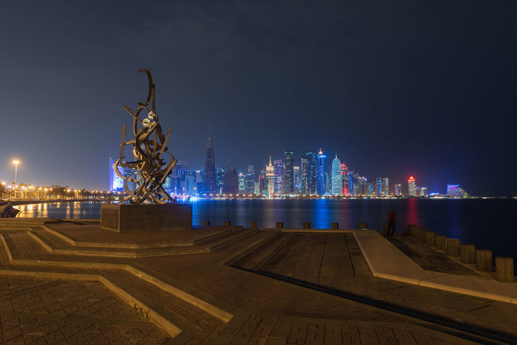 Doha, Qatar Architecture Night Illuminated Building Exterior Built Structure City Sky Building Sculpture Cityscape Tall - High No People Nature Statue Art And Craft Representation Water Office Building Exterior Urban Skyline Human Representation Outdoors Modern Skyscraper Doha Qatar Middle East Sclupture Travel