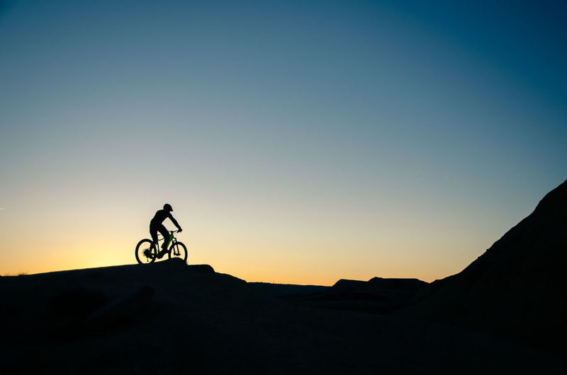 Silhouette person riding bicycle on mountain against clear sky
