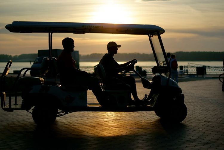 Man Riding Golf Cart On Street Against Cloudy Sky During Sunset