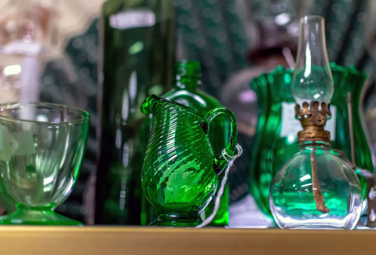Decorative green glass pitchers, vases and bottles are for sale at a vintage antique shop