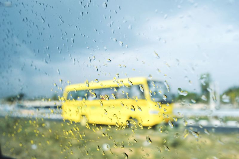 Drop Water Wet Rain Glass - Material Window RainDrop Rainy Season No People Yellow Droplet Weather Water Drop Focus On Foreground Close-up Day Land Vehicle Indoors  Nature Sky