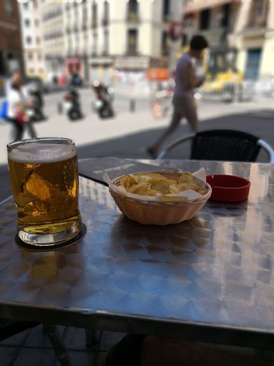 Close-up of beer glass and potato chips on table at restaurant