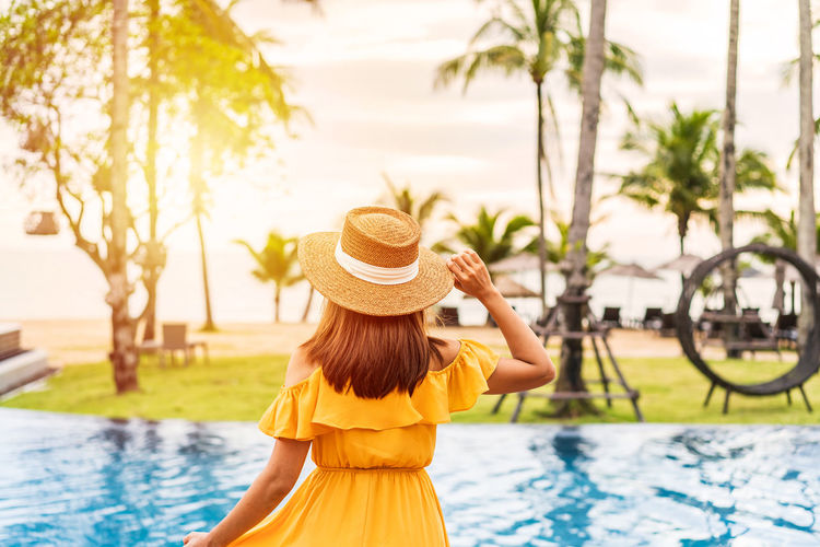 Rear view of woman wearing hat swimming pool