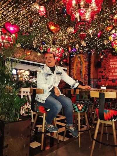 Full Length Young Women Nightclub Portrait Illuminated Sitting Chair Christmas Decoration Celebration Nightlife