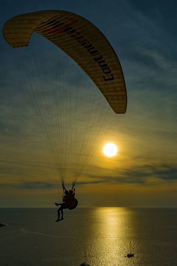 Silhouette Friends Paragliding Over Sea Against Sky During Sunset