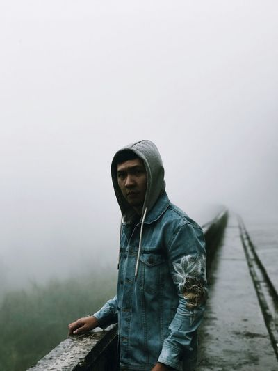 Portrait of man standing by retaining wall during foggy weather