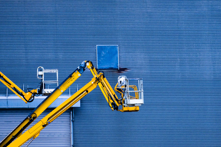 Low Angle View Of Cherry Picker Against Blue Patterned Wall